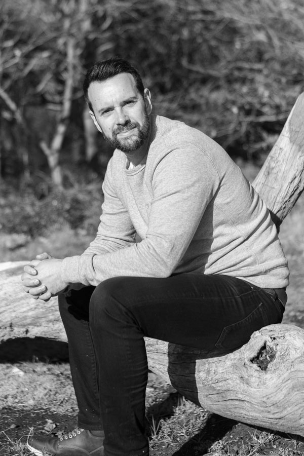Mono natural light personal branding portrait of seated man on a log