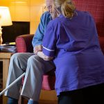 Eldery man being given support by a nurse carer in a Nursing Care Home for testimonial Healthcare Homes
