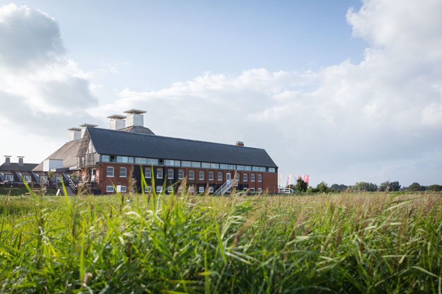 Snape Maltings with blue sky and green grass rule of thirds
