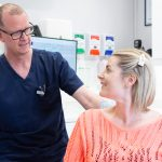 A male dentist talking to his female patient
